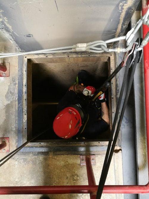 Adgangshul til siloen. Arbejderen er iført fuldt ATEX iltværn og udstyr.